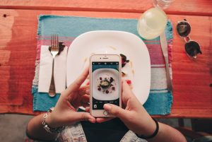 person taking picture of their food using mobile phone